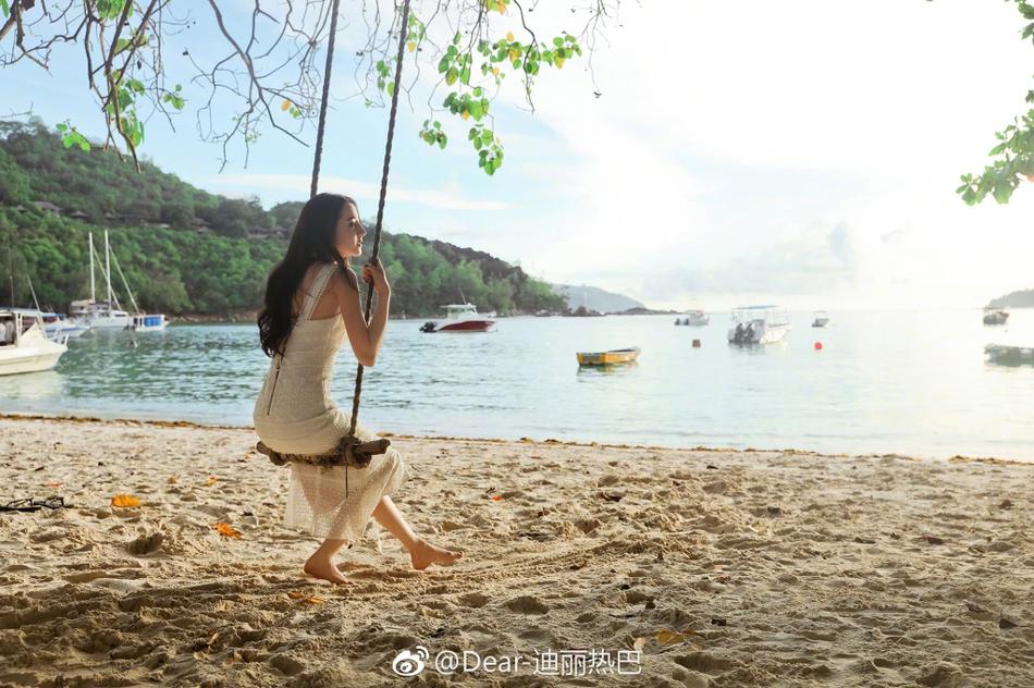 迪丽热巴海边穿白裙荡秋千 笑容清纯美如画