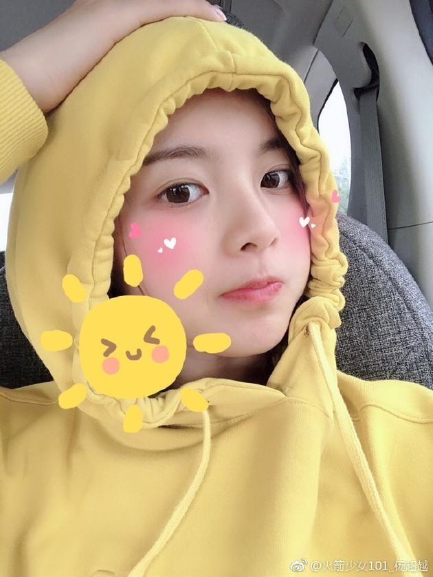 照片中,杨超越戴着黄色卫衣上的帽子,一脸素颜,嘟嘴卖萌,十分的可爱