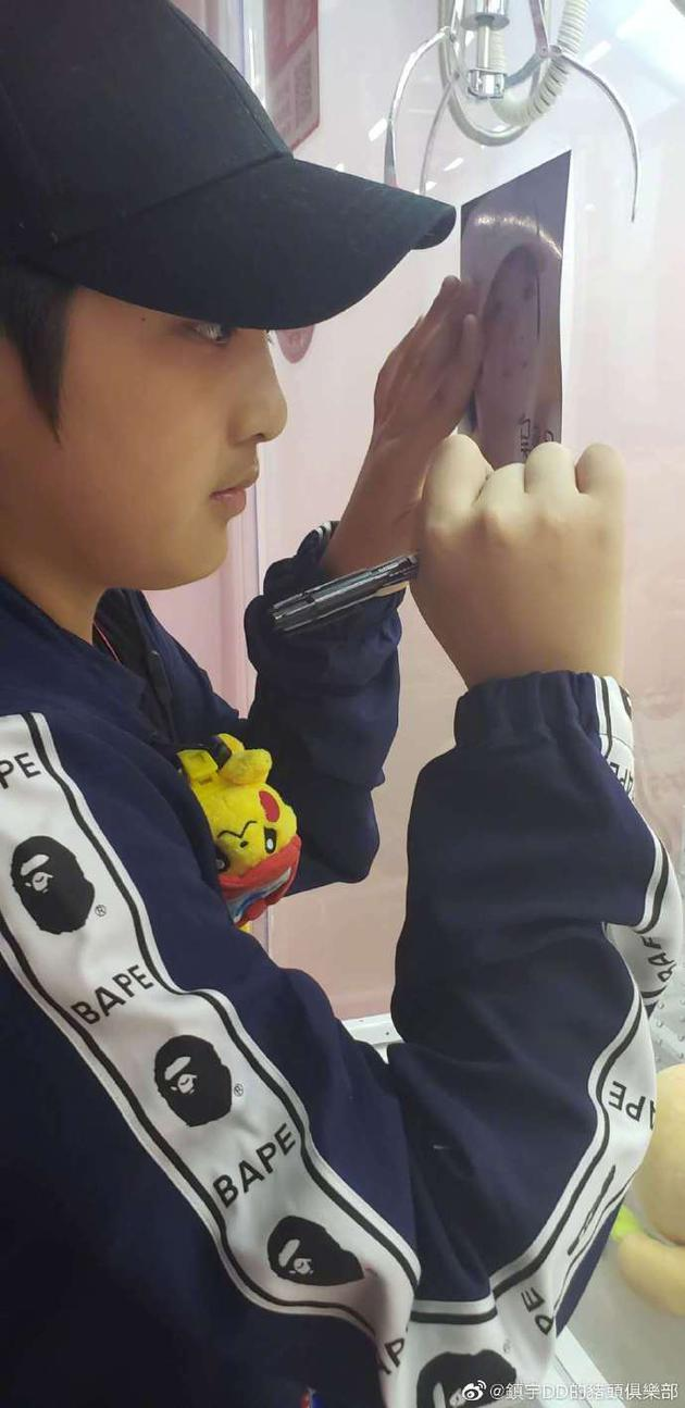 吴镇宇晒近照儿子费曼头戴棒球帽练习认真签名充气娃娃制图片